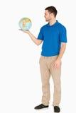 在他的掌上型计算机的新销售人员藏品地球 免版税图库摄影