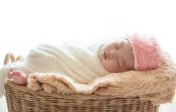 在他的放松在丝毫下的棕色篮子的新出生的男婴睡眠 免版税库存照片