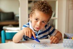 在他的服务台的迷人的小男孩繁忙的着色 免版税库存照片