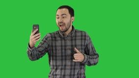 在他的电话的年轻博客作者录音录影,当走在一个绿色屏幕,色度钥匙上时 影视素材