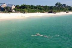 在他的白种人年轻人游泳往岸在海 白色沙子、海滩小屋和绿浪在一好日子 顶视图 免版税库存图片
