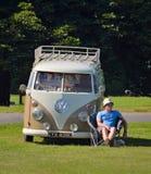 在他的经典大众露营者货车旁边供以人员坐在夏天太阳的椅子 免版税图库摄影