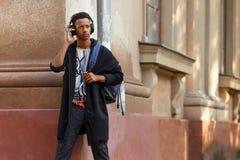 在他的耳机的行家年轻人听的音乐,在街道,与拷贝空间的图象 库存图片