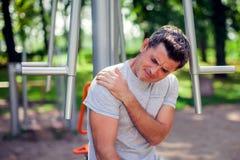 在他的肩膀的人感觉在t的痛苦在体育期间和锻炼 库存图片