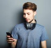 在他的脖子和微笑的wh的英俊的年轻人佩带的耳机 库存图片