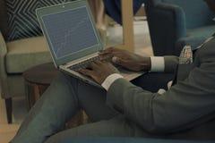 在他的膝部的商人佩带的衣服藏品膝上型计算机和调查开户图 免版税库存照片