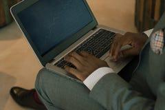在他的膝部的商人佩带的衣服藏品膝上型计算机和调查开户图 免版税图库摄影