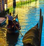 在他的长平底船的平底船的船夫划船在一条威尼斯式运河在一个夏日 库存照片