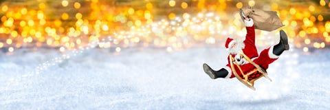在他的雪橇雪金黄bokeh backgro的疯狂的圣诞老人飞行 免版税库存照片