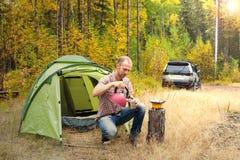 在他的露营地供以人员坐在秋天森林里 库存图片