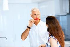 在他的面孔旁边供以人员拿着一个红辣椒 免版税图库摄影