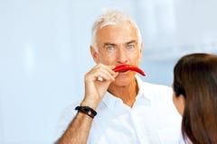 在他的面孔旁边供以人员拿着一个红辣椒 库存照片