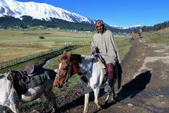 在他的马的牛仔骑马在古尔马尔格,印度 免版税库存照片