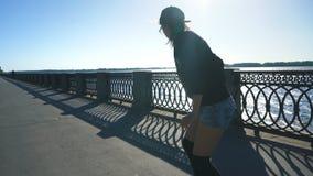 在他的longboard的美好的女孩骑马在堤防附近的路 极其体育运动 股票录像