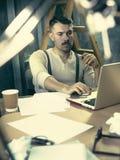 在他笔记本和键入检查他即将来临的会议细节一个有胡子的商人的画象 库存图片