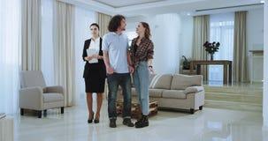 在代表的一名宽敞大房子年轻已婚夫妇和有吸引力的不动产房地产经纪商新房 影视素材