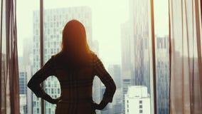 在令人惊讶的日落期间,年轻成功的妇女剪影敬佩从窗口的城市视图在办公室 库存照片