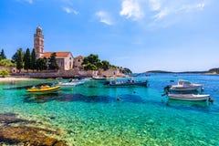 在令人惊讶的群岛的看法有在镇赫瓦尔,克罗地亚前面的小船的 亚得里亚海的港口hvar海岛老城镇 普遍旅游 库存照片