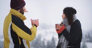 在令人惊讶的风景中间的好友与多雪的森林,喝一些热的饮料得到温暖在冻结的天 股票录像