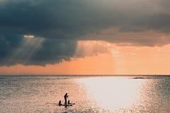 在以后的雷暴背景的日落场面 有三个孩子的一个父亲在两个委员会用浆划 家庭一口用浆划 图库摄影