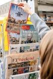 在以ISIS加州为特色的新闻报亭的妇女买的时代杂志 库存照片
