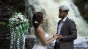 在仪式的年轻婚礼夫妇在瀑布附近 股票录像