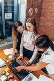 在任务的三位女性大学生使用在家站立的膝上型计算机 免版税库存照片