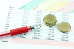 在企业图表的红色笔和金钱硬币。 库存图片