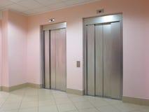 在企业大厅的两个闭合的电梯 免版税库存照片