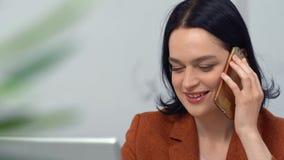 在企业样式工作的美丽的Brunnete在办公室 女孩答复电话微笑 影视素材