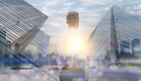 在企业概念、人身分和神色的两次曝光通过与大厦和大厦背景的都市风景 免版税库存照片
