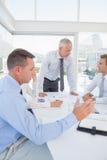 在企业生意人有照相机的服务台附近倾斜查找会议其他坐的微笑的小组 免版税库存照片