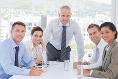 在企业生意人有照相机的服务台附近倾斜查找会议其他坐的微笑的小组 免版税库存图片