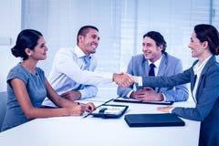 在企业生意人有照相机的服务台附近倾斜查找会议其他坐的微笑的小组 库存图片