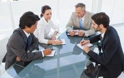 在企业生意人有照相机的服务台附近倾斜查找会议其他坐的微笑的小组 免版税图库摄影
