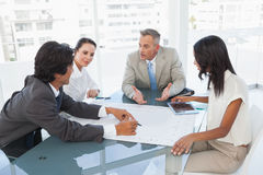 在企业生意人有照相机的服务台附近倾斜查找会议其他坐的微笑的小组 图库摄影