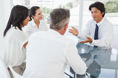 在企业生意人有照相机的服务台附近倾斜查找会议其他坐的微笑的小组 库存照片