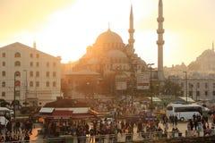 在伊斯坦布尔的日落在海港附近拥挤了正方形有在清真寺的看法 免版税库存图片