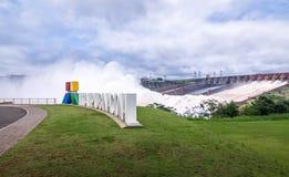 在伊泰普水电站水坝标志的溢洪道-巴西和巴拉圭边界 库存图片