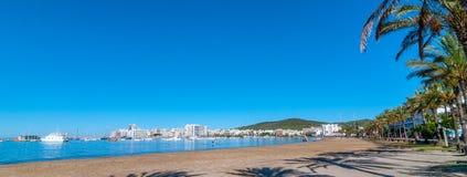 在伊维萨岛江边的被放弃的风船 走在距离的海滩的人们 人用浆划他的委员会往海滩 免版税库存图片