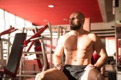在休息在健身房的锻炼以后的肌肉人 免版税库存图片