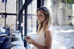在休闲时间,聪明的妇女在她的数字式片剂读了文本 免版税库存图片