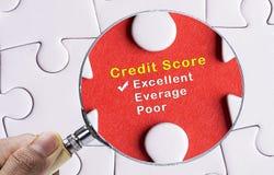 在优秀信用评分评价表的放大镜焦点。 库存照片