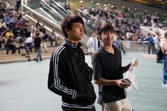 在优胜者打赌的年轻观众 免版税图库摄影