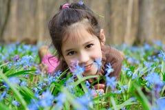 在会开蓝色钟形花的草之中的女孩 免版税库存照片