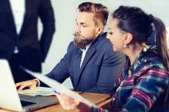 在会议在内部现代明亮的办公室和工作的企业队在膝上型计算机 免版税库存照片