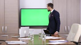 在会议室指向绿色屏幕大模型电视的商人 影视素材