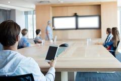 在会议室时供以人员拿着片剂,当参加一次会议 免版税库存照片