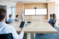 在会议室时供以人员拿着片剂,当参加一次会议 库存照片