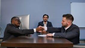 在会议期间,握手的商人密封与他的伙伴的一个成交 库存图片